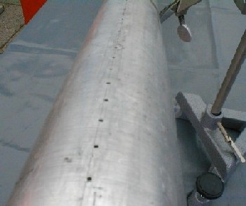 Metal tube with long row of drilled holes